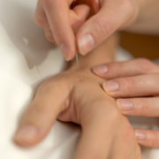 Acupuncture needles being applied in hand, via Fort Saskatchewan Acupuncture.